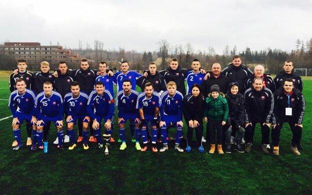 Víťazné mužstvo a realizačný tím s trofejou.