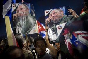 Ľudia počas zhromaždenia na Castrovu pamiatku držia plagáty s jeho podobizňou.