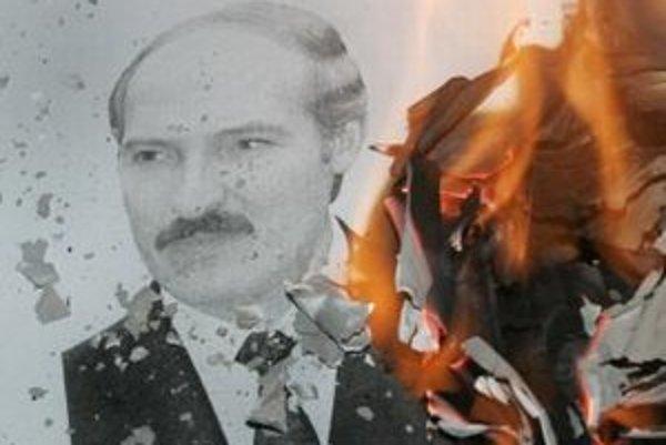 Demonštrant páli fotografiu bieloruského prezidenta Alexandra Lukašenka.