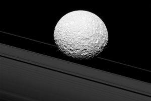 Môže to vyzerať, že mesiac Mimas preráža cez prstence Saturnu. V skutočnosti je mesiac od prstencov vzdialený 45-tisíc kilometrov.