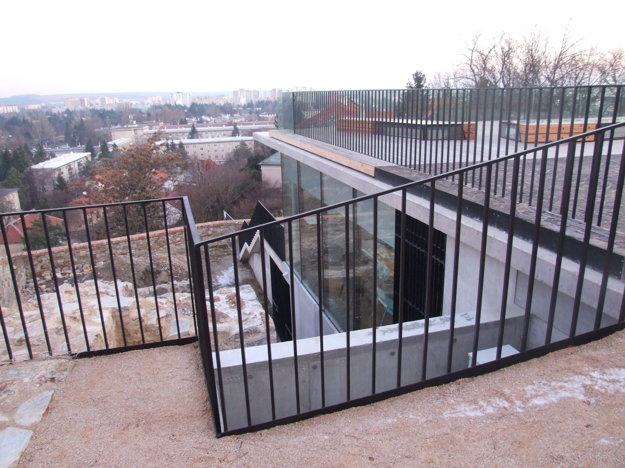 Kaviareň je pod úrovňou terénu. Vpravo vidieť sedenie na streche, vľavo pod kovovou zábranou sú hradby.