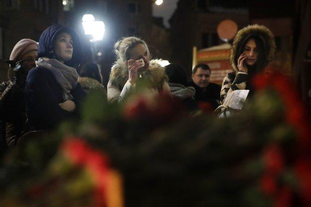 Pred moskovskú budovu zboru prichádzajú ľudia a kladú kvety a zapaľujú sviečky.