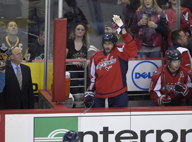 Alexander Ovečkin zdraví aplaudujúci dav po tom, ako zaznamenal svoj tisíci bod v NHL.