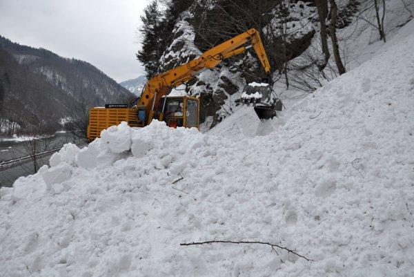 Bager odpratáva sneh z koľajníc.