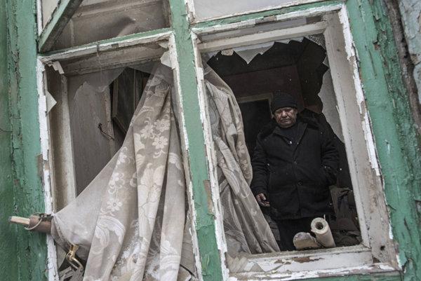 Muž stojí v zničenom byte v ukrajinskej Avdijivke.