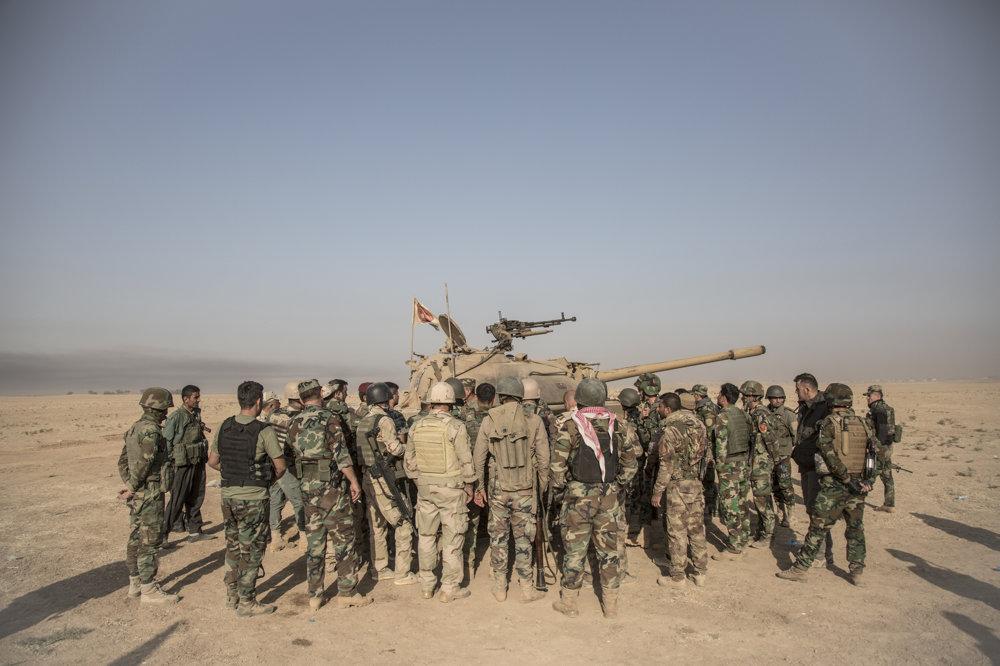 Kurdskí pešmergovia sa zhromaždili okolo tela mŕtveho tankistu.