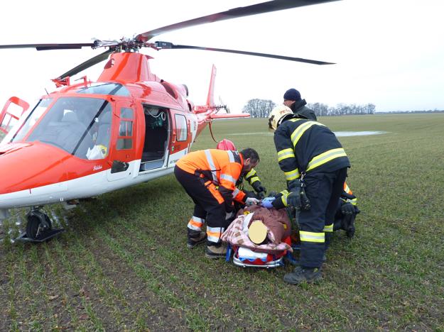 Zraneného nakladajú do vrtuľníka.