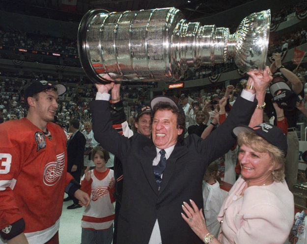 Na snímke zo 17. júna 1998 Mike Ilitch dvíha nad hlavu Stanleyho pohár. Po jeho pravici stojí Igor Larionov.
