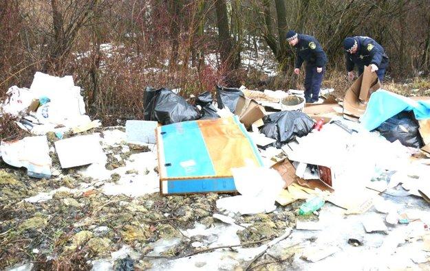 Policajti hľadajú v kope smetí dôkazy.
