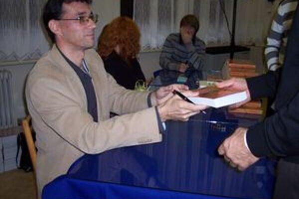 Michal Baňanka pri podpisovaní svojej prvej knihy. V hlave už vraj nosí námety na ďalšiu.