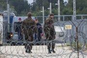 Maďarskí vojaci a policajti hliadkujú pozdĺž plota s ostnatým drôtom na tranzitnej zóne pri meste Tompa.
