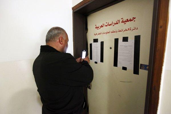 Muž stojí pri zapečatenej kancelárii palestínskeho kartografa Chálila Tufagdžího.