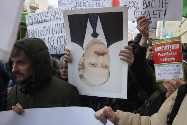 Jeden z protestujúcich v Minsku drží prezidentov portrét obrátene na znak odporu.