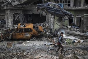 Chlapec na bicykli prechádza cez zničený Mosul.
