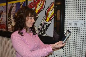 Ľudmila Štecová. Riaditeľka MMUAW ukazuje, ako treba QR kódy zoskenovať.