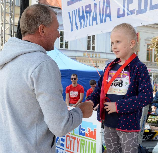 Igor Kováč. Dekoruje víťazku behu na 100 m Nelku Kucákovú.