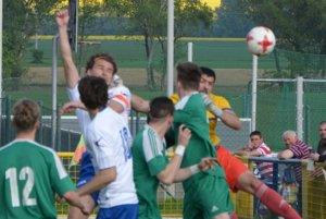Kapitán Hrušovian Peter Kurbel posiela loptu hlavou do siete a Hrušovany vedú 1:0.