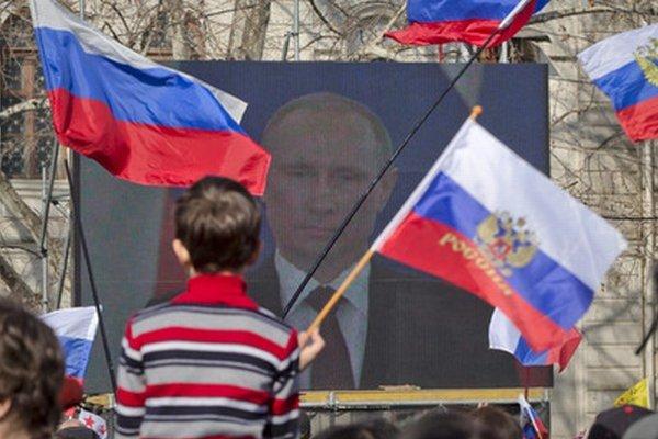 Chlapec v Sevastopole sleduje prejav ruského prezidenta Vladimira Putina o Kryme.