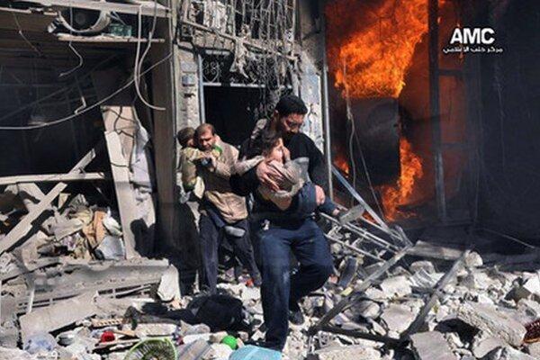 Sýrčania pomáhajú deťom z horiacej budovy v meste Aleppo.