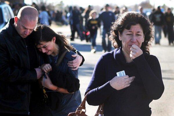 Žena čaká na svoje dieťa pred školou, kde došlo k streľbe.