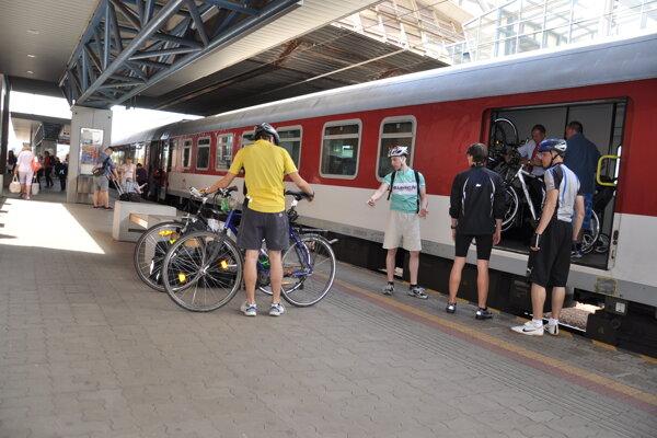 Cyklisti si nakladajú svoje bicykle do pojazdnej úschovne batožiny.