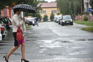 Na snímke žena s dáždnikom kráča po ulici počas dažďa v Trebišov.