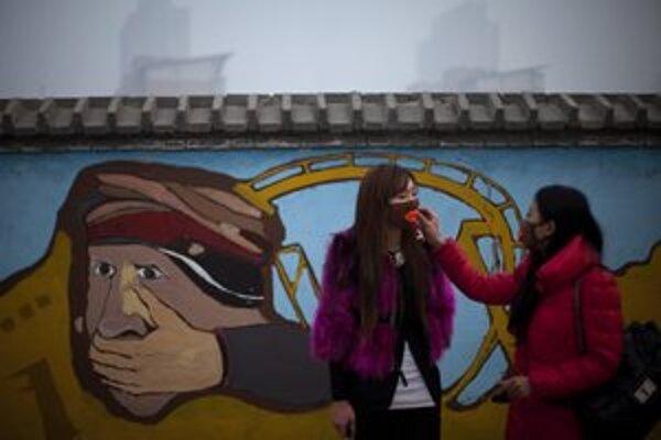 Žena napráva kamarátke masku v zábavnom parku v Pekingu.