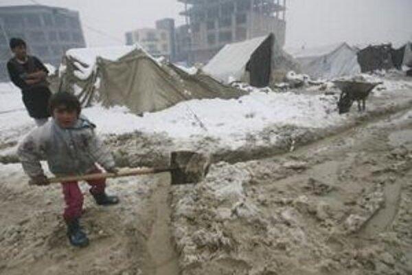 Afganský chlapec - utečenec, odpratáva sneh spred svojho improvizovaného domova v Kábule.