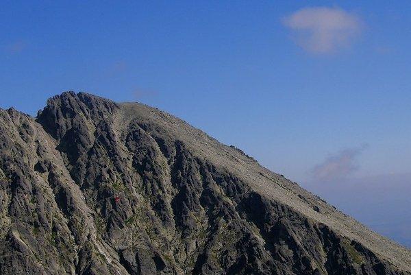 Vrchol Huncovského štítu a jeho zrázy do Skalnatej doliny. Výrazný žľab zo Skalnatej doliny, vedúci do Huncovského sedla (vľavo od vrcholu) láka zdanlivou jednoduchosťou aj menej skúsených turistov, hoci je bez vodcu zakázaný, nevedie doň turistický chodník.