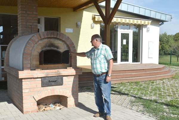 Starosta Čerhova Pavol Balogh pri funkčnej peci na chlieb v tradičnej podobe, v pozadí turistická informačná kancelária.