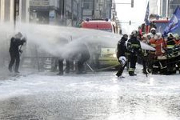 Požiarnici striekajú vodu z hadice , keď sa snažia prejsť cez policajnú zátarasu pri sídle premiéra v Bruseli.