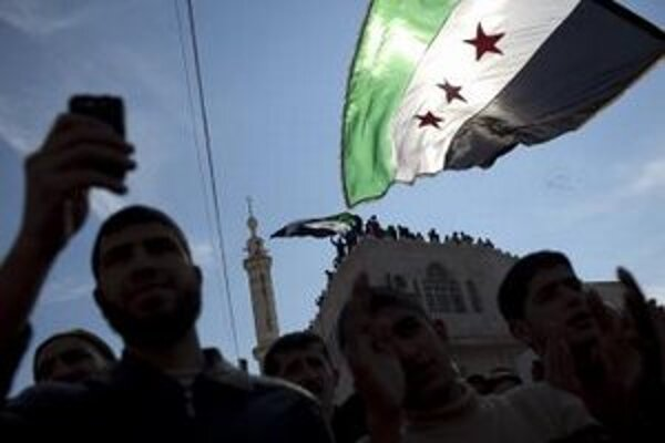 Sýrčania mávajú revolučnými sýrskymi zástavami na protivládnom proteste.
