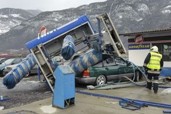 Požiarnik sa pozerá na zničené auto, ktoré zdemolovalo prevrátené zariadenie autoumyvárne na benzínke vo švajčiarskom Saillone.