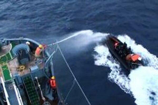 Člen posádky veľrybárskej lode používa proti ochranárom vodné delo.