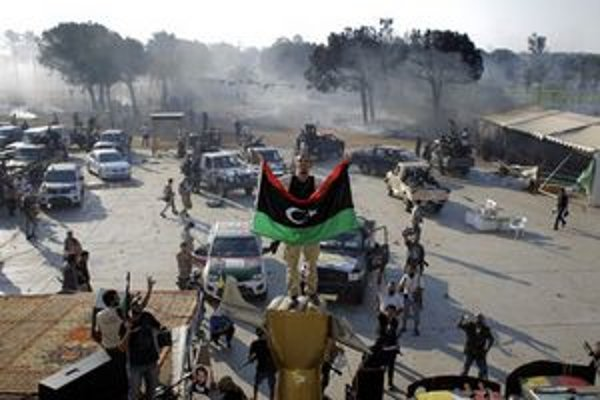 Povstalec stojí so zástavou na soche v komplexe Báb al-Azízíja.