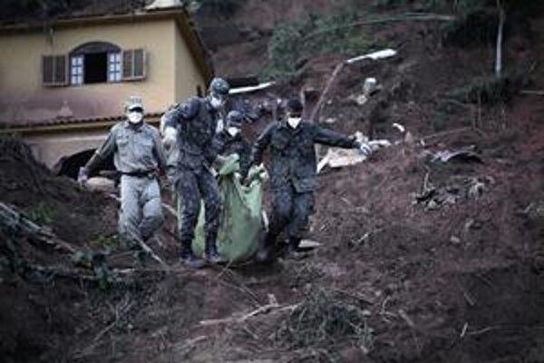 Vojaci znášajú telo mladého človeka, ktorý sa stal jednou zo stoviek obetí zosuvov.