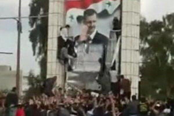 Na sníme z videozáznamu demonštranti strhávajú podobizeň prezidenta Assada v meste Dará.