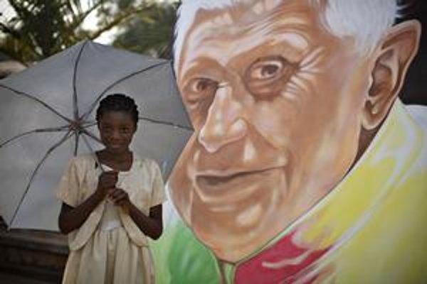 Jedenásťročná Kamerunčanka Larissa stojí pred portrétom Benedikta XVI.