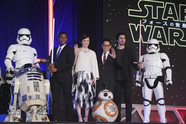 Herci a režisér Abrams pózujú na pódiu počas premiéry nových Hviezdnych vojen.