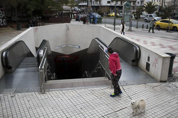 Žena so psom stojí pred vchodom do stanice metra v Aténach.