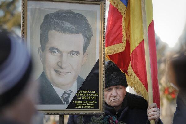 Starší muž drží obraz s podobizňou Nikolaea Ceausescua, ilustračná snímka.