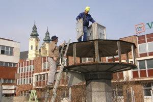 Hodiny svetového času pred Orbisom sú minulosťou. Na rebríku stojí výtvarník Jaroslav Košš.