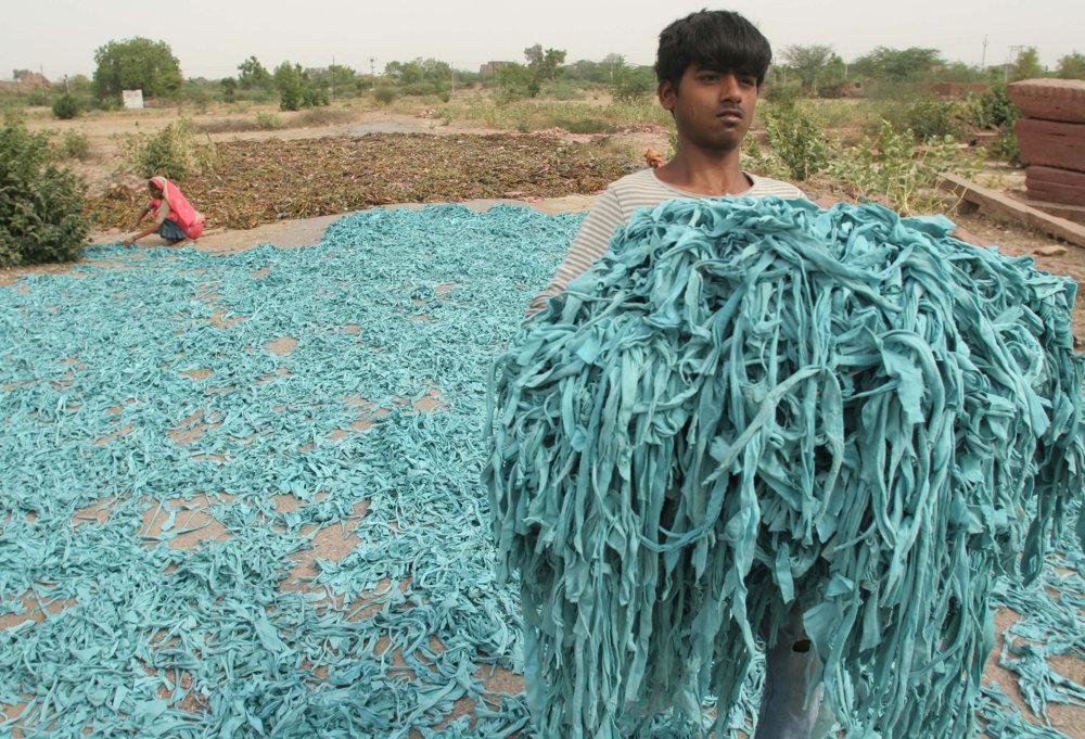 Muž prenáša útržky textílií, vedľajšieho produktu textilnej výroby, po farbení a sušení v severoindickom meste Fatehpur Sikri