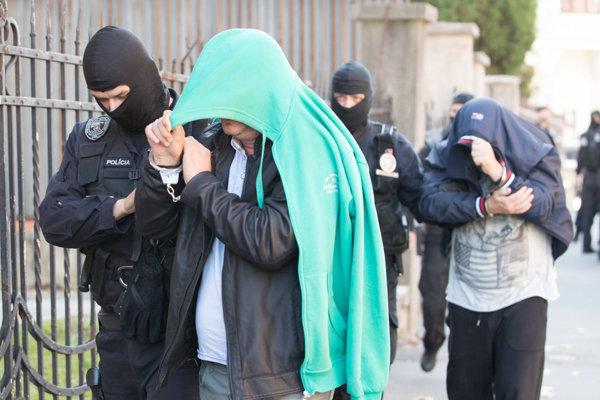 Október 2017. Eskorty predvádzajú 13 obvinených na súd.