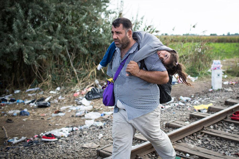Utečenci prechádzajú cez ilegálny hraničný prechod pri maďarskom mestečku Röszke na maďarsko-srbských hraniciach. (14. 9. 2015, Röszke, Maďarsko)