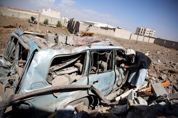 Muž prezerá zničené auto po leteckom útoku v Saná.