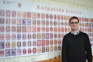 Etnograf Jozef Fundák. Pri baneri zobrazujúcom batikované kraslice z nášho regiónu.