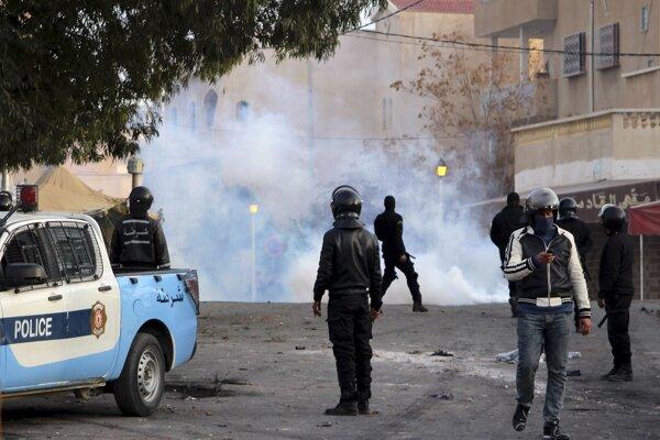 Policajti stoja za clonou so slzotvorným plynom počas zrážok s demonštrantmi v tuniskom meste Kasrajn.