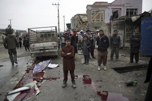 Miestni obyvatelia kráčajú okolo miesta, kde došlo k samovražednému bombovému útoku.