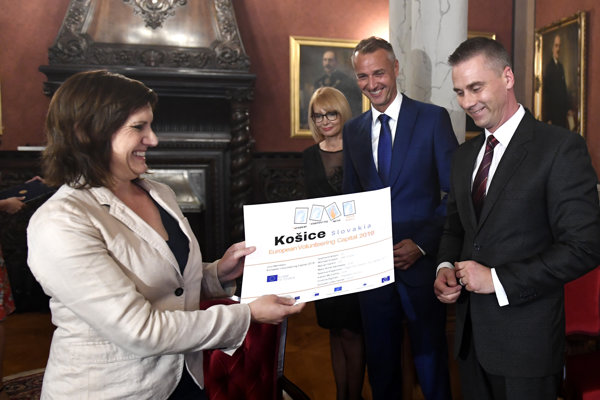 Riaditeľka Európskeho dobrovoľníckeho centra Gabriella Civico (vľavo) odovzdáva certifikát Košice – Európske mesto dobrovoľníctva 2019 viceprimátorovi Košíc Martinovi Petruškovi (vpravo). Druhá zľava viceprimátorka Košíc Renáta Lenártová a podpredseda vlády SR pre investície a informatizáciu Richard Raši.